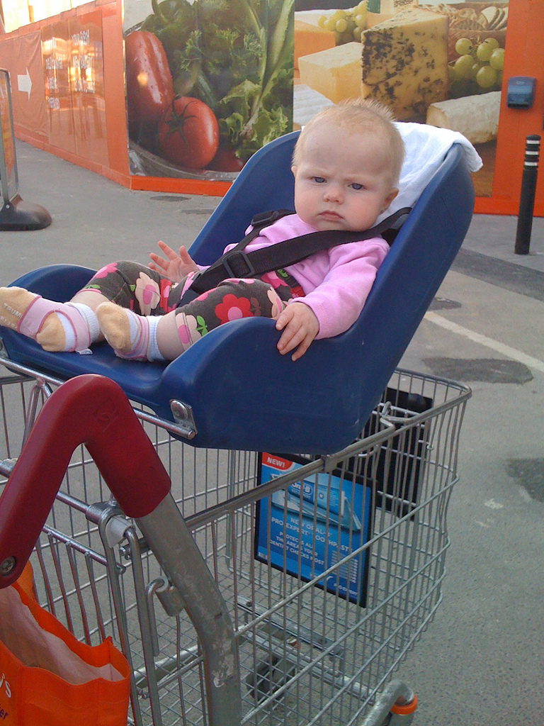Grimmig dreinschauendes Baby sitzt im Einkaufswagen