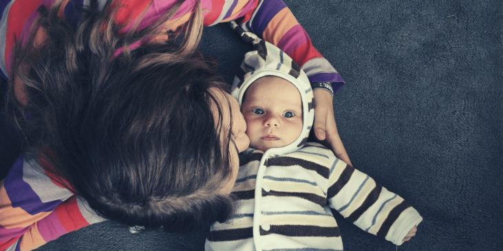 Mutter küsst ihr Baby zärtlich auf die Wange