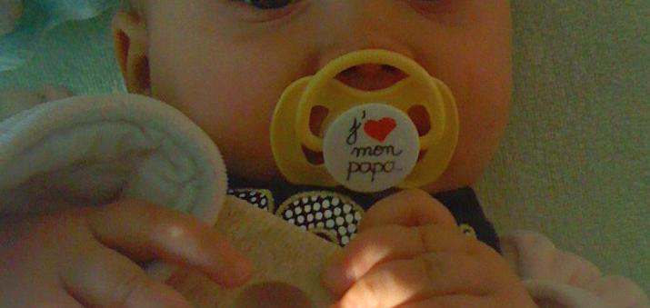 Schnuller im Mund eines Babys mkit der Aufschrift j´aime mon Papa