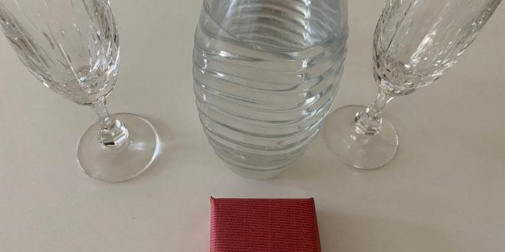 Hochzeitsantrag - Verpackter Ring vor Gläsern