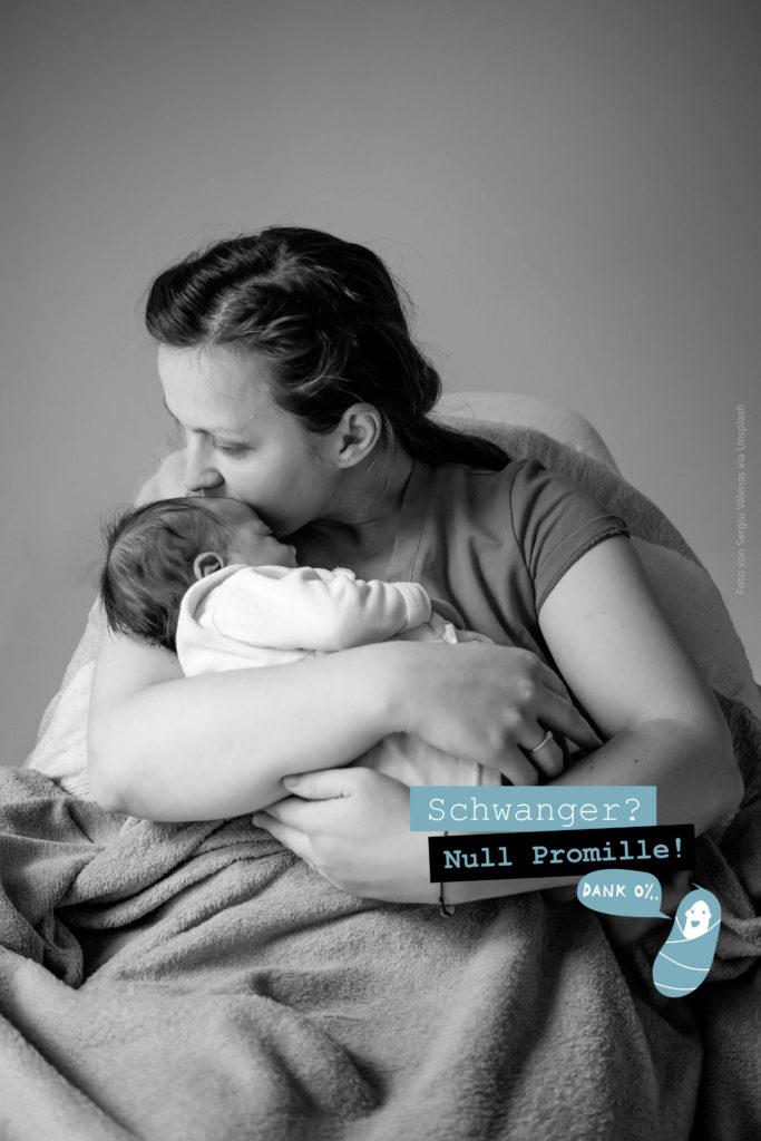 Mutter hält Baby im Arm und küsst es auf die Stirn