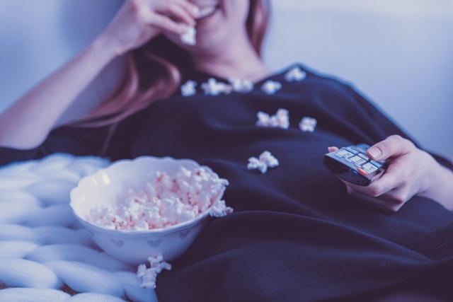 Schwangere Frau schaut Schwangerschaftsfilme und isst Popcorn