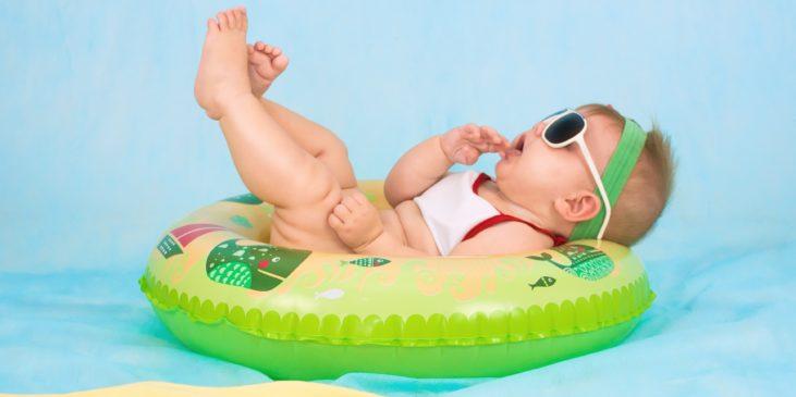 Baby chillt mit Sonnenbrille im Schwimmreifen